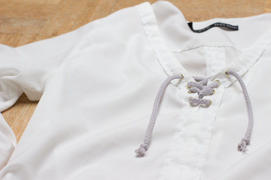 Do you have an old blouse in your closet? Follow this easy refashion tutorial for a DIY lace up blouse and wear it all summer long!